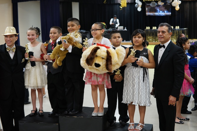 Jorge Alonso Perez, executive director of Dancing With the Children (left), stands with Edgewood ISD ballroom dance competition winners and Robert Ramirez, dance instructor (right). Photo courtesy of Nuvo Multimedia.