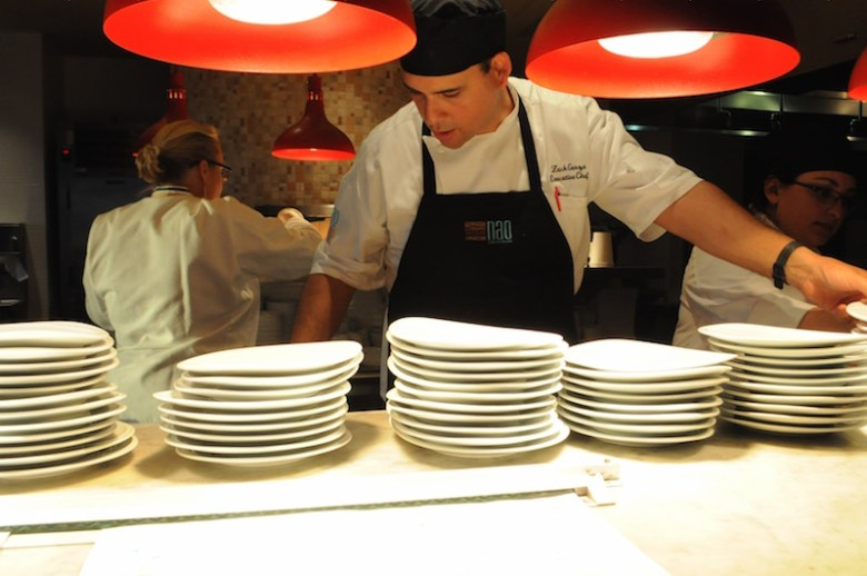 Executive Chef Zach Garza arranges plates for the next dinner course. Photo by Lea Thompson
