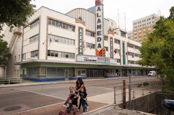 A family passes by the Alameda Theater on their way East on Houston Street. Photo by Scott Ball.