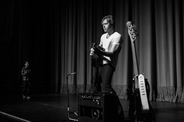 Erik Sanden tests a guiter onstage prior to the show. Photo by Scott Ball.