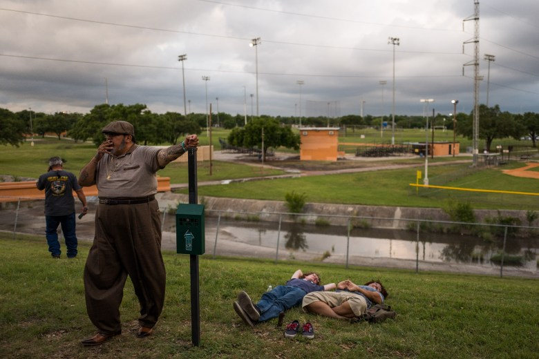 A couple take a break on the lawn as others make cell phone calls and smoke breaks away from the loud speakers. Photo by Scott Ball.