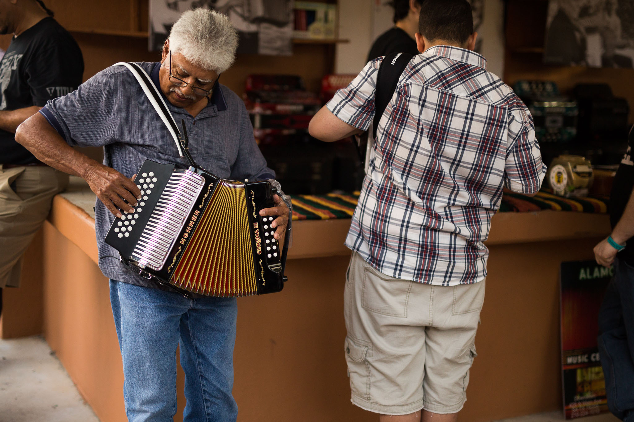 Lane Fuentes tries out an accordion from a pop-up shop from Alamo Music Store. Photo by Scott Ball.