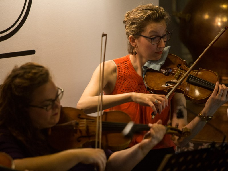 Violinist Anastasia Parker (right) plays her violin during a performance at Dor?ol Distillery. Photo by Scott Ball.