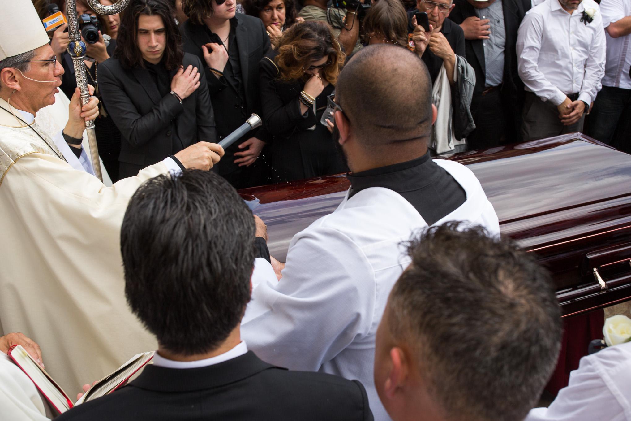 Archbishop Gustavo-García-Siller sprinkles holy water over the casket of Emilio Navaira. Photo by Scott Ball.