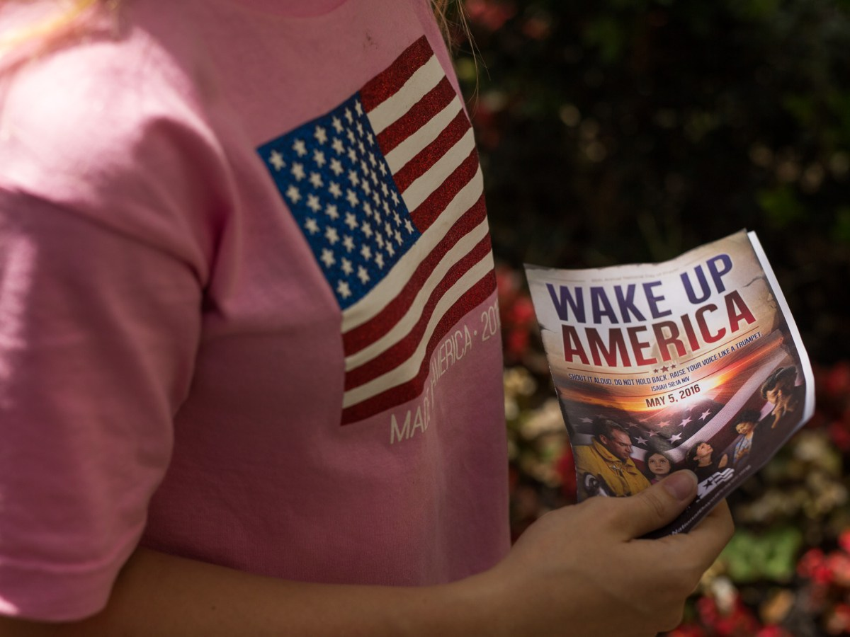 Timber Williams holds up a program that is titled 'Wake Up America'. Photo by Scott Ball.