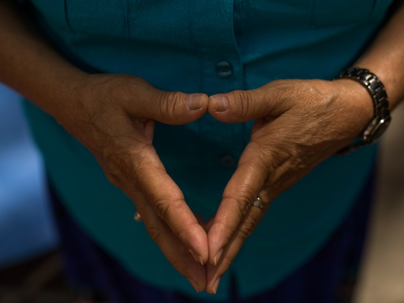 A woman holds her hands together as she prays. Photo by Scott Ball.