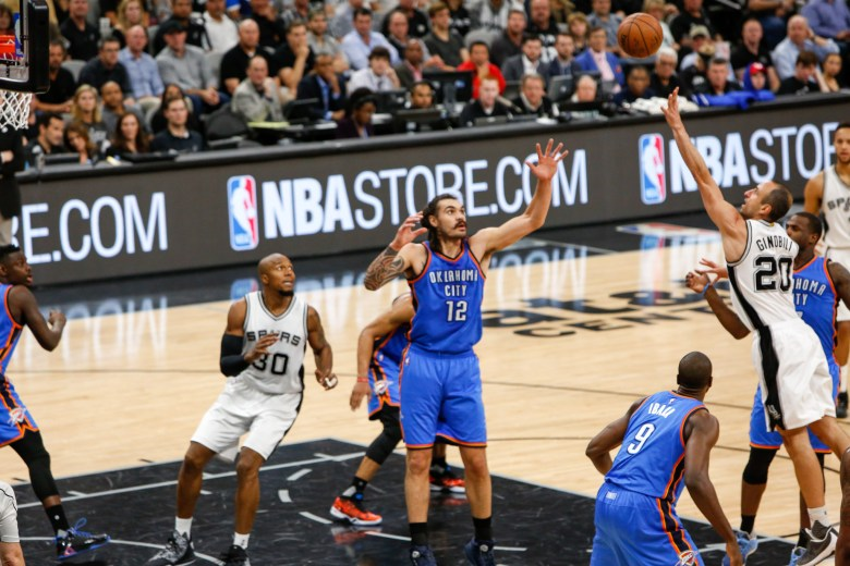 Spurs Forward Manu Ginobili pushes the ball into air over defender #12 Steven Adams. Photo by Scott Ball.