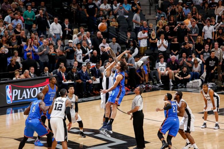 Spurs Center #21 Tim Duncan and Thunder Center #12 Steven Adams jump for the opening tip-off. Photo by Scott Ball.