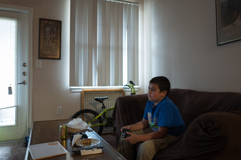 Joseph eats dinner as he plays video games after he arrives home from Stewart Elementary. Photo by Scott Ball.