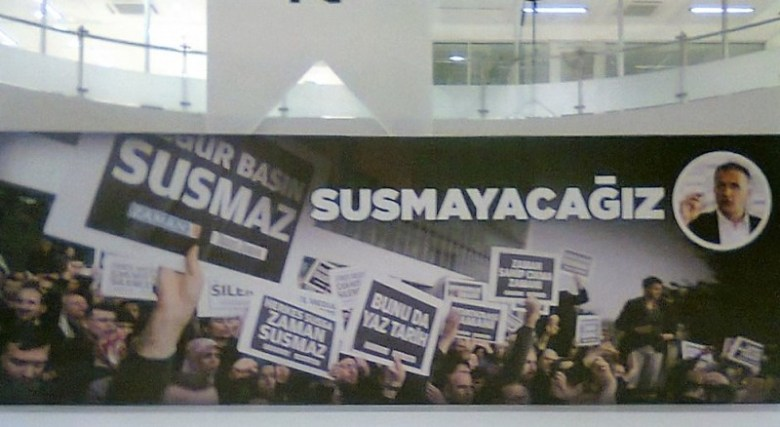 """Banner that hung inside of the Zaman building in June 2015 until the seizure saying """"We Will Not Be Silenced."""" Photo at the top right corner is Ekrem Dumanli, former Editor in Chief. Photo by Kathy Hamilton."""