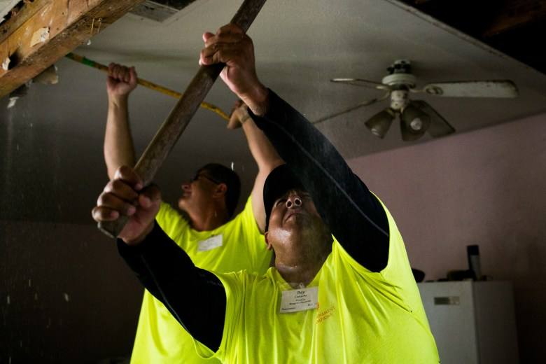 H-E-B volunteer Rey Camacho works to pull apart the celling of Jennifer Miller's home to begin the process of repairing leaks. Photo by Kathryn Boyd-Batstone.