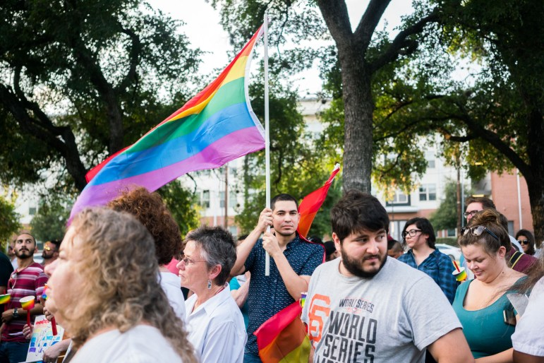 Community members hold up flags in support of LGBTQIA community during the vigil held for lives lost in Orlando during the mass shooting. Photo by Kathryn Boyd-Batstone.