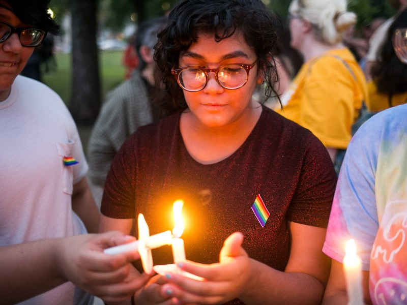 From left: Nathaniel Barrera and Joely Mojica light candles in honor of those who passed away in Orlando. Photo by Kathryn Boyd-Batstone.