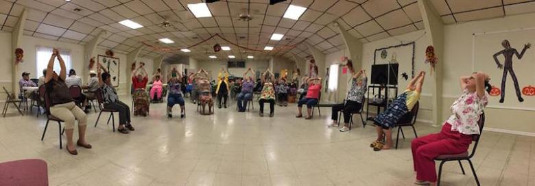 A group of senior citizens at St. Timothy Catholic Church practice chair yoga.  Photo courtesy of Yoga Day.