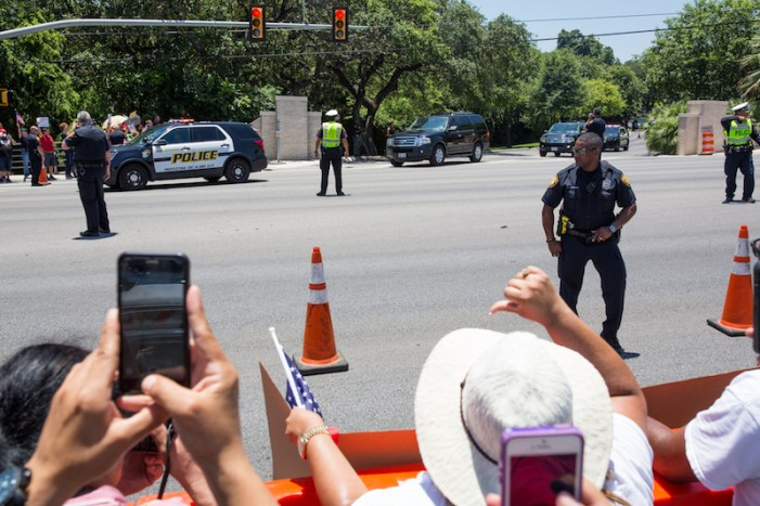 A demonstrator records Donald Trump's motorcade as it departs Oak Hills Country Club.  Photo by Michael Cirlos.