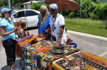 A community member speaks with Mr. and Mrs. Harris about their experiences in Ghana and the origin of the pieces that they sell.