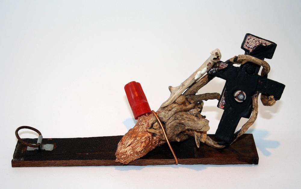 Cu., 2016, cat jaw bone, copper, wire, crucifix, root, wood, acrylic, by Alejandro Augustine Padilla. Photo courtesy of Ruiz-Healy Art.