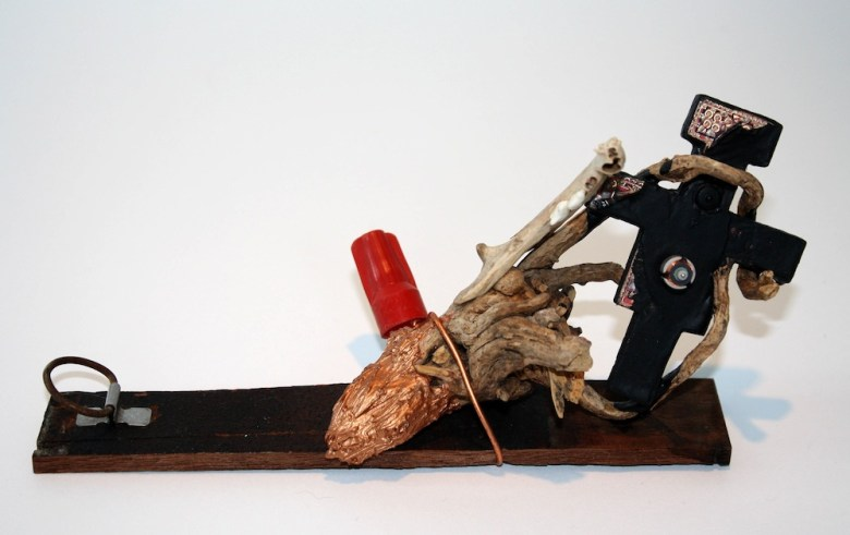Cu., 2016, cat jaw bone, copper, wire, crucifix, root, wood, acrylic, by Alejandro Augustine Padilla.  Photo courtesy of Ruiz-Healy Art.