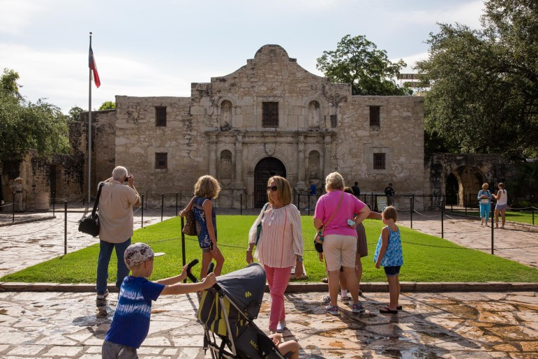Tourists stop by and visit the front of The Alamo. Photo by Scott Ball.