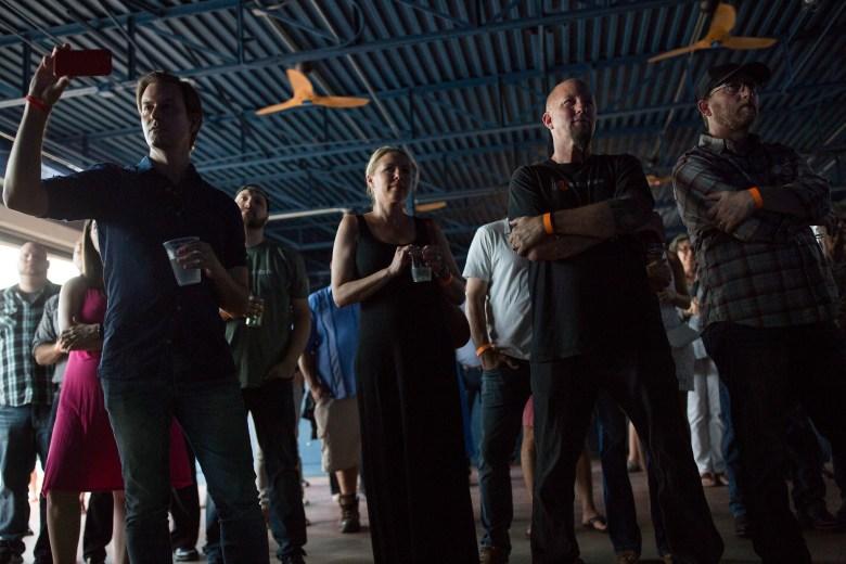TechBloc Co-founder David Heard (left) takes a photograph during a short film remembering Alan Weinkrantz. Photo by Scott Ball.