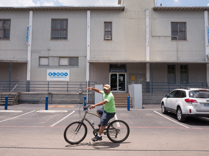 A cyclist rides by the Blue Star Contemporary. Photo by Scott Ball.
