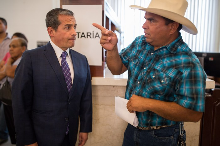 Mexican Consul General of Mexico in San Antonio Héctor Velasco Monroy speaks to Santiago Castillo, a visitor at the Mexican Consulate. Photo by Scott Ball.