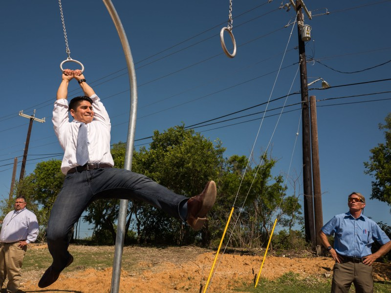 Councilman Rey Saldana (D4) attempts to swing on chained rings in the fitness area of Pearsall Park. Photo by Scott Ball.