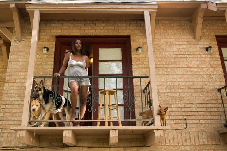 """Ramona Trevino stands on her balcony as a result of hearing the protest from across the street in her home at The Reserve at Pecan Valley. Ramona has had two abortions in her life, one when she was 17, and the other when she was 22. """"I regret the decisions I made to this day"""". Photo by Scott Ball."""