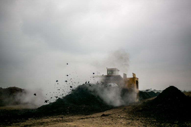 To spread moisture and improve air circulation, heavy equipment turns and mixes the compost piles. Photo by Kathryn Boyd-Batstone.
