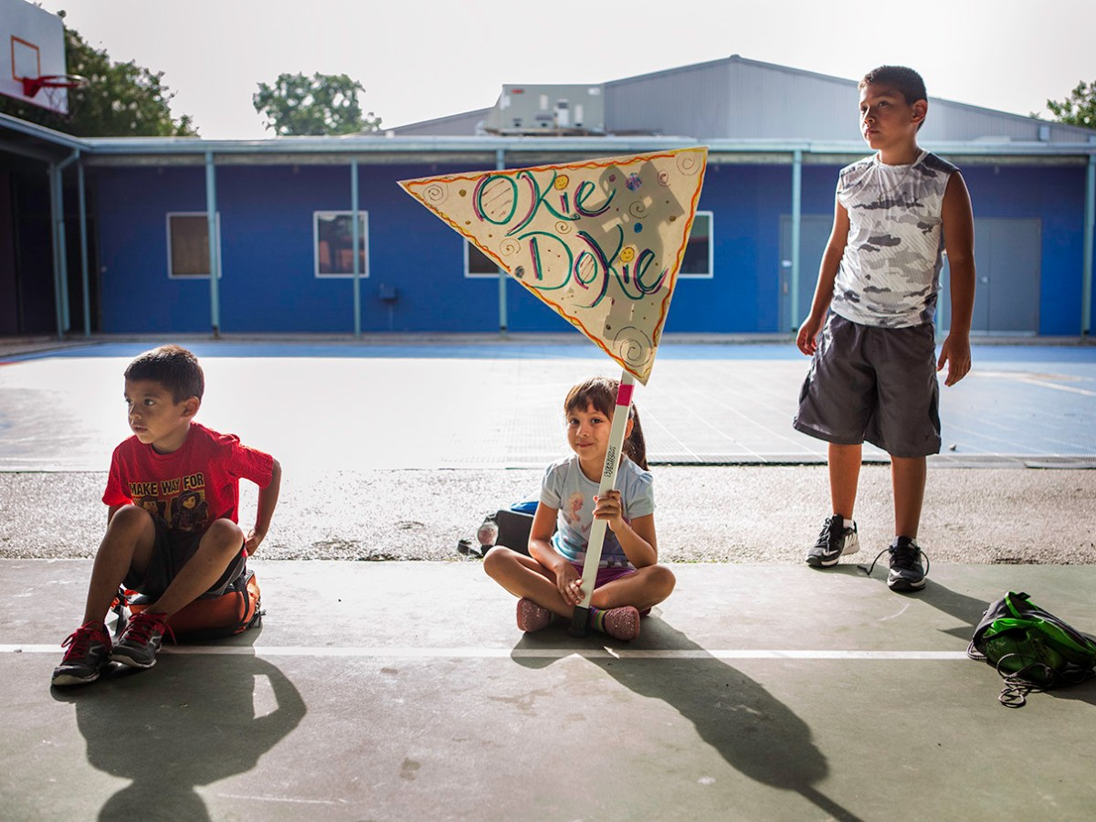 From left: Giovanni, Delanie, and Xavier look on as the morning activities take place. Photo by Kathryn Boyd-Batstone.