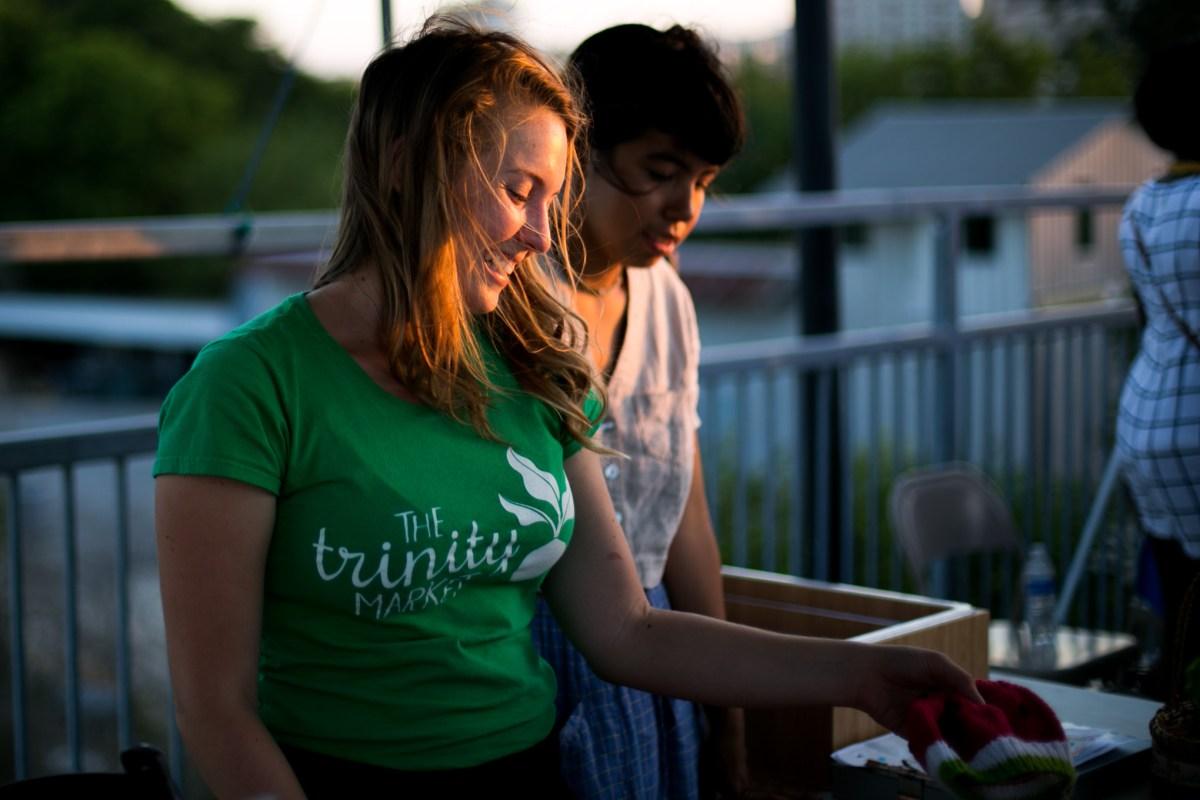 Trinity Farmers Market founder Hayley Sayrs shows merchandise to customers. Photo by Kathryn Boyd-Batstone