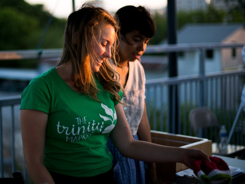 Trinity Farmers Market founder Hayley Sayrs shows merchandise to customers. Photo by Kathryn Boyd-Batstone