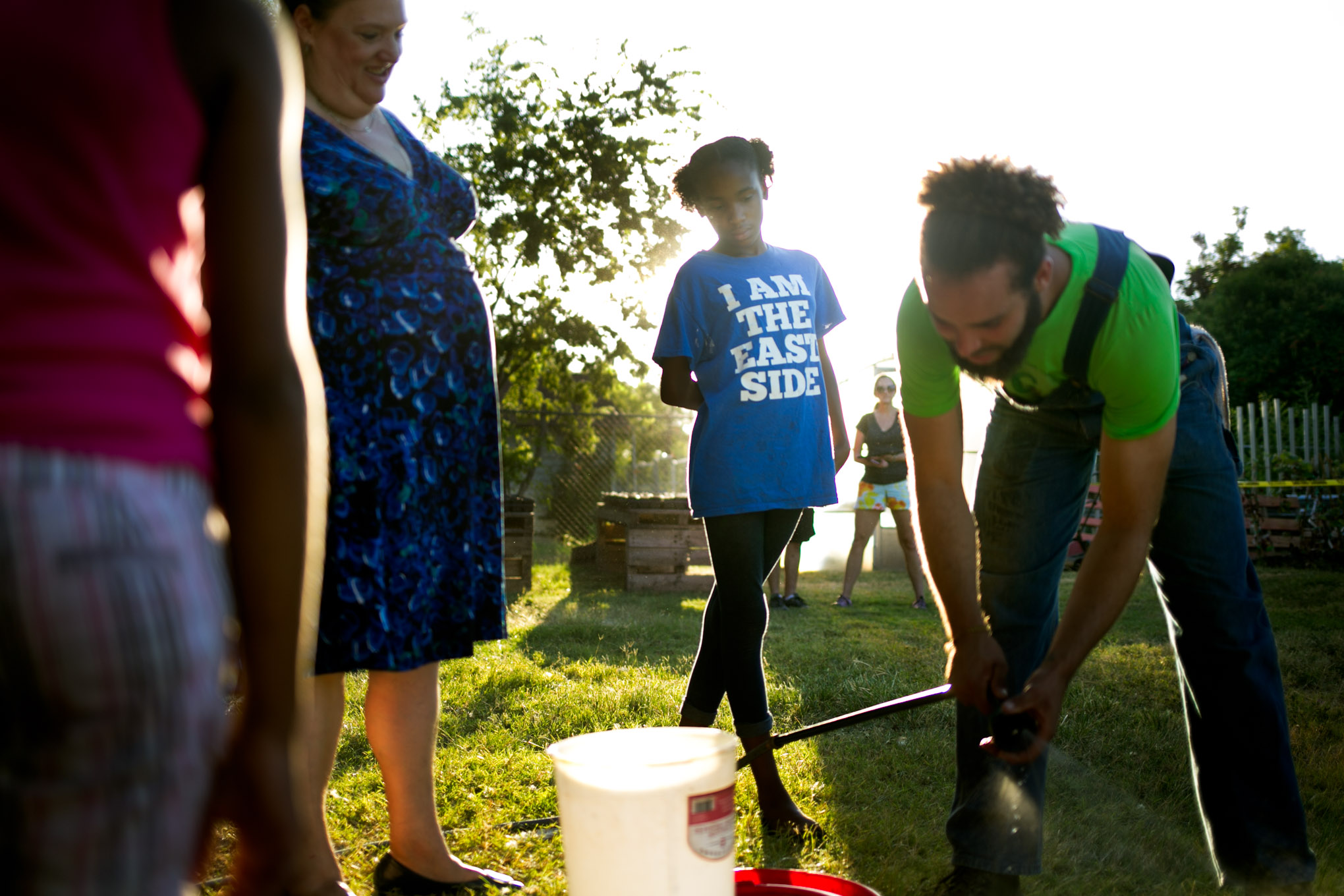 Kionna watches Gardopia founder Stephen Lucke prepare water for the chickens. Photo by Kathryn Boyd-Batstone.