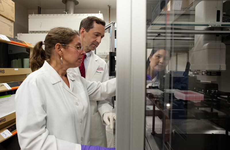 VRC scientists working with a Biomark Nxp robot, which is used to set up and harvest cultures of HIV patients' B cells that are used in the discovery of novel HIV neutralizing antibodies. Photo courtesy of NIAID.