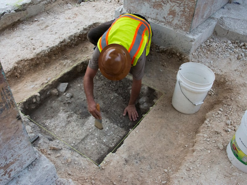 An archaeologist brushes an area of what is believed to be remnants of a bordering wall of the Alamo. Courtesy photo.