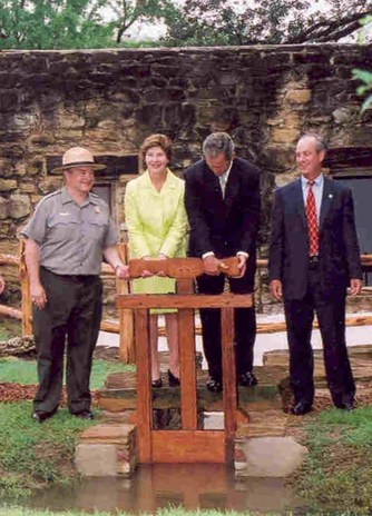 "President George W. Bush and First Lady Laura Bush at the 2000 inauguration of the restored Grist Mill at Mission San José. The two men to the far left and right in the photo are only identified as ""Ricardo"" and ""Steve."" Photo courtesy of the National Park Service."