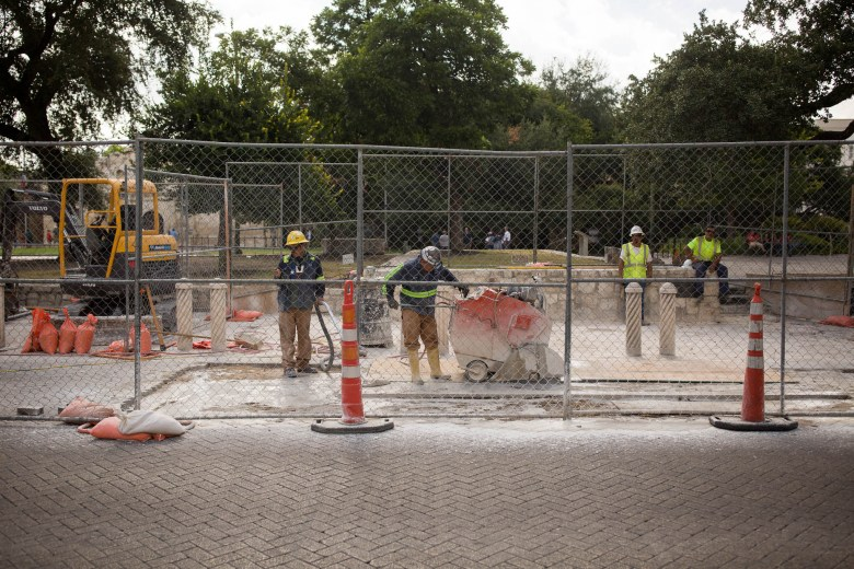 Construction workers cut the top layer of stone from a future dig site at Alamo Plaza. Photo by Scott Ball.
