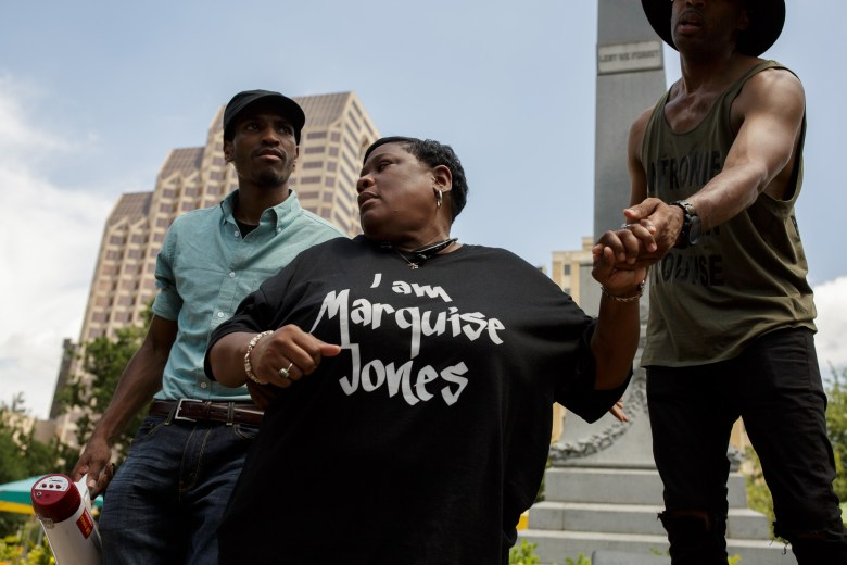 Mike Lowe (right) and Johnathan-David Jones (left) helped Debbie Bush, the aunt of slain Marquise Jones, step down from a ledge.  Photo by Scott Ball.
