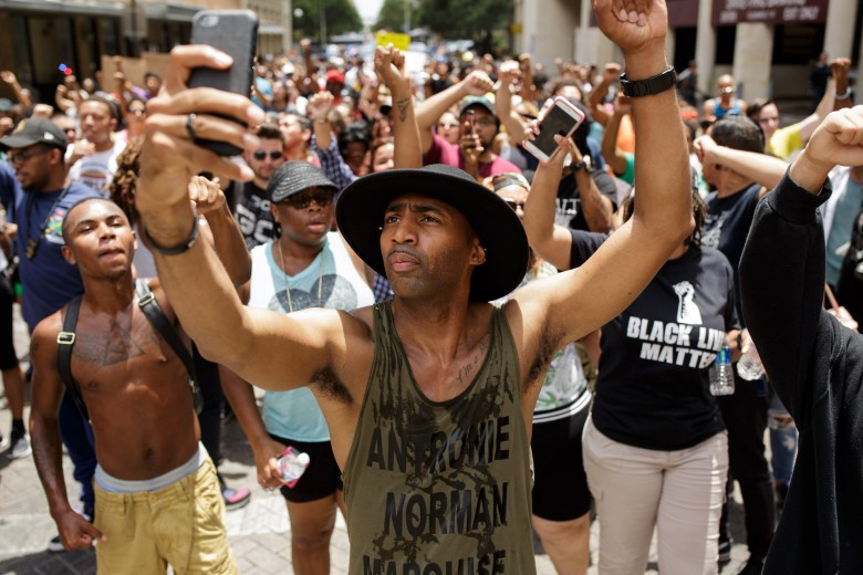 Local activist and organizer Mike Lowe leads the march while documenting the event on his smartphone. Photo by Scott Ball.