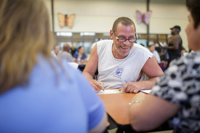 Haven for Hope resident Frank Carrasquillo fills out paperwork while discussing options and cracking jokes with fair vendors. Photo by Scott Ball.
