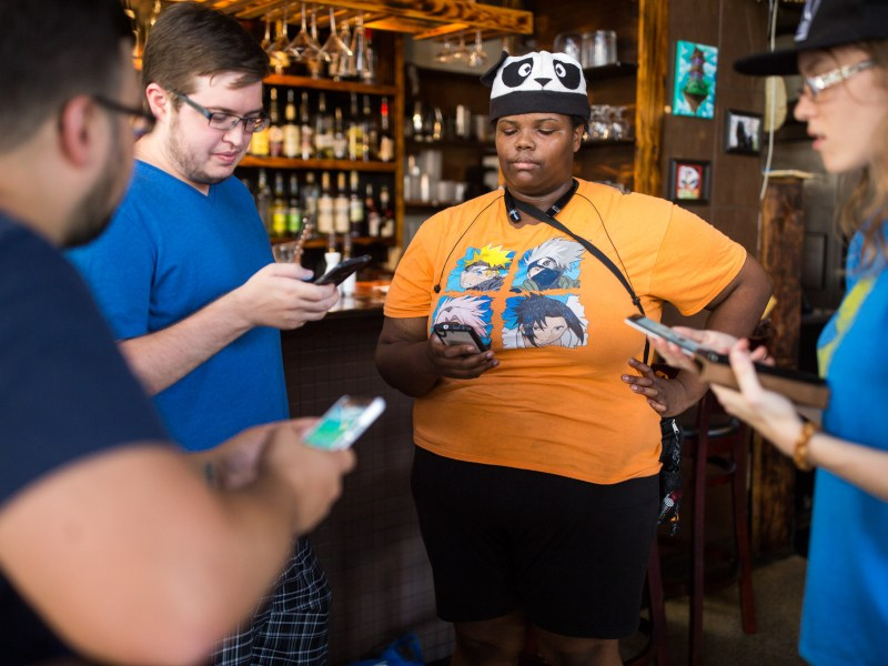 (left to right) Justin Horton, Ben Miller, Panda, and Ruthie Longwell form a circle as they play Pokémon Go at Kimura. Photo by Scott Ball.
