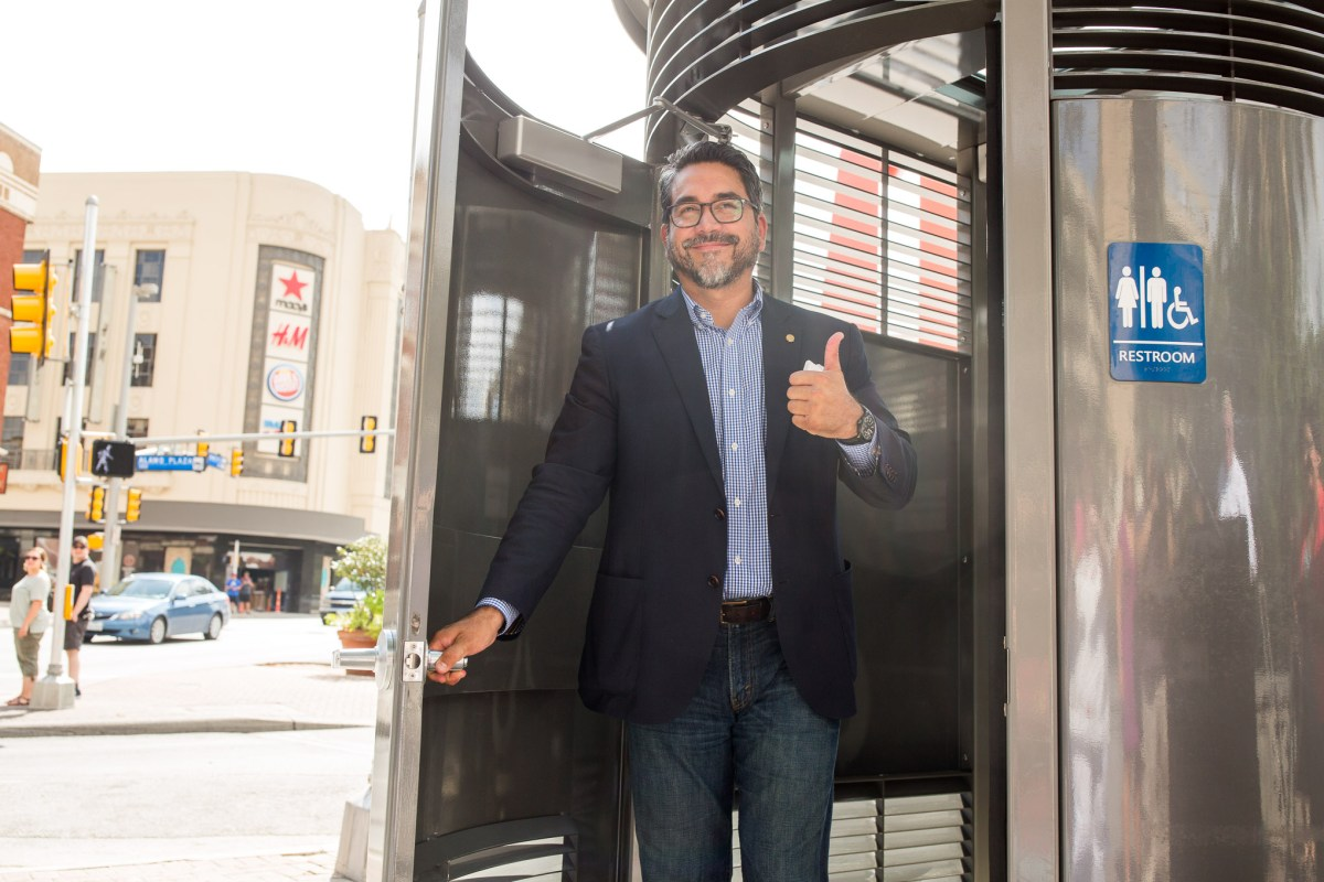 Councilman Roberto Treviño (D1) exits the restroom after it's first official use. Photo by Scott Ball.