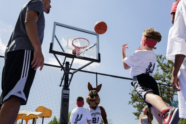 Children throw the ball up into the air as Danny Green and the Spurs Coyote look on. Photo by Scott Ball.