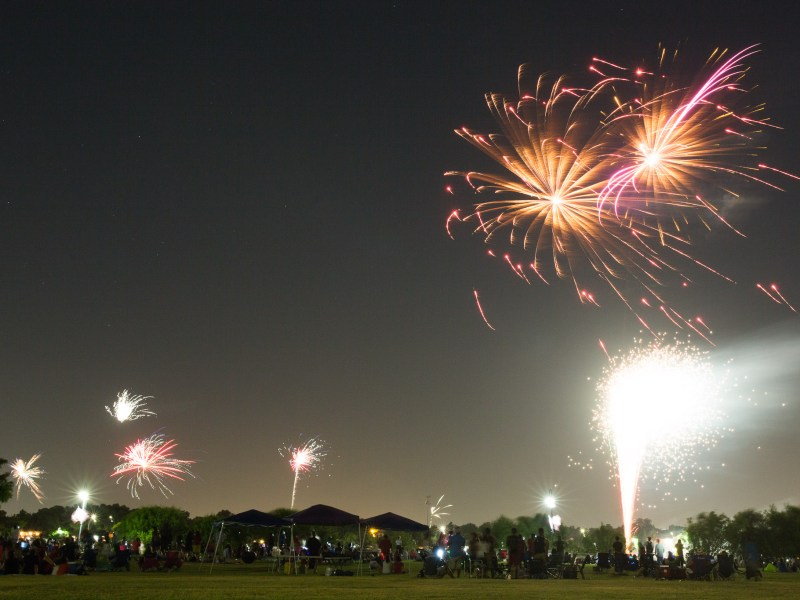 Fireworks are set off at Woodlawn Lake and nearby houses in the neighborhood in the distance. Photo by Scott Ball.