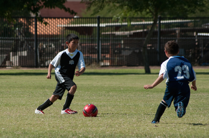Two young boys chase the ball during a soccer match. Photo by Joel Agee via Flickr.