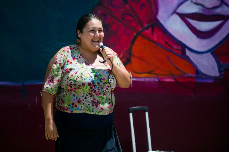 Martinez Street Women's Center Executive Director Andrea Figueroa explains they held community meetings to make sure the mural reflects the community. Photo by Kathryn Boyd-Batstone.