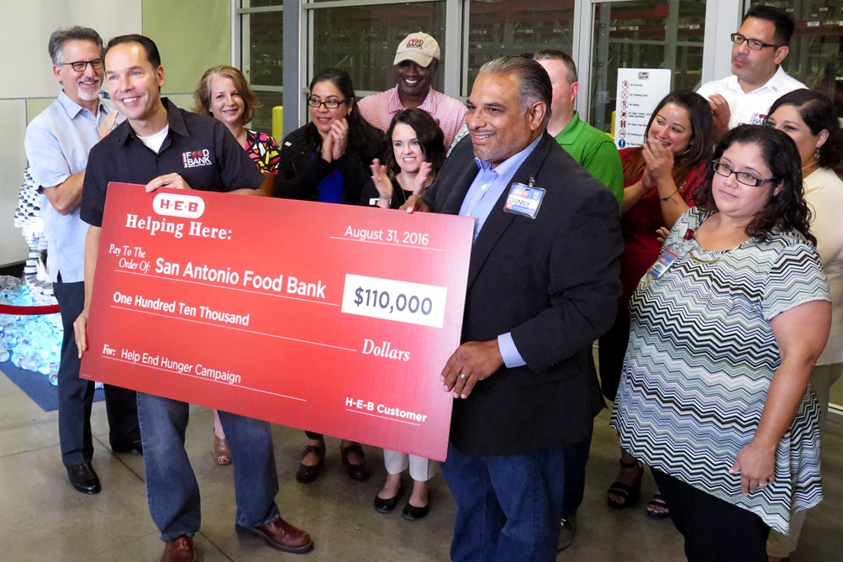 CEO of the San Antonio Food Bank, Eric Cooper, receives a $110,000 donation from H-E-B representative Danny Flores as part of the grocer's End Hunger Campaign.