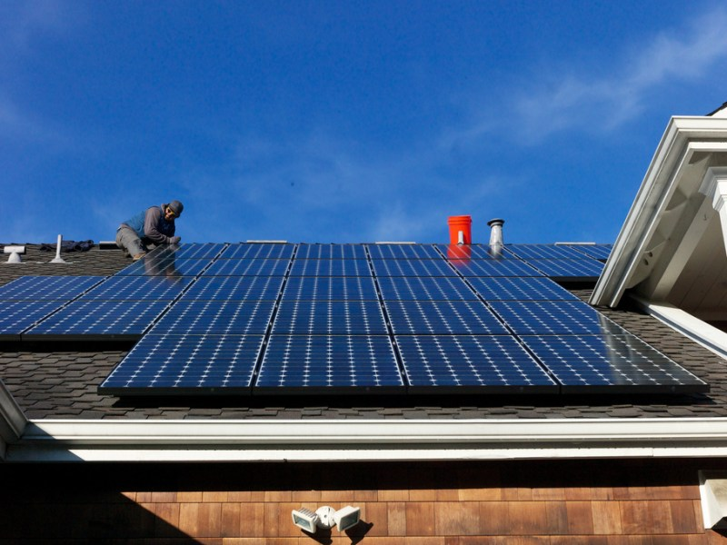 An array of solar panels is installed on a residential roof. Creative commons photo by Flickr user Jon Callas.