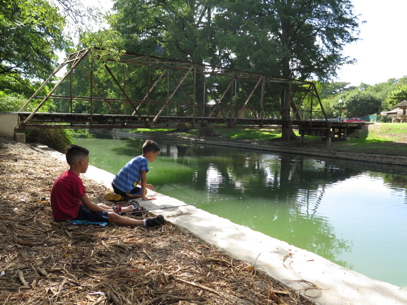 From left: Julián and Jayden watch ducks and play with a fishing rod on the river in Brackenridge Park. Photo by Rocío Guenther.