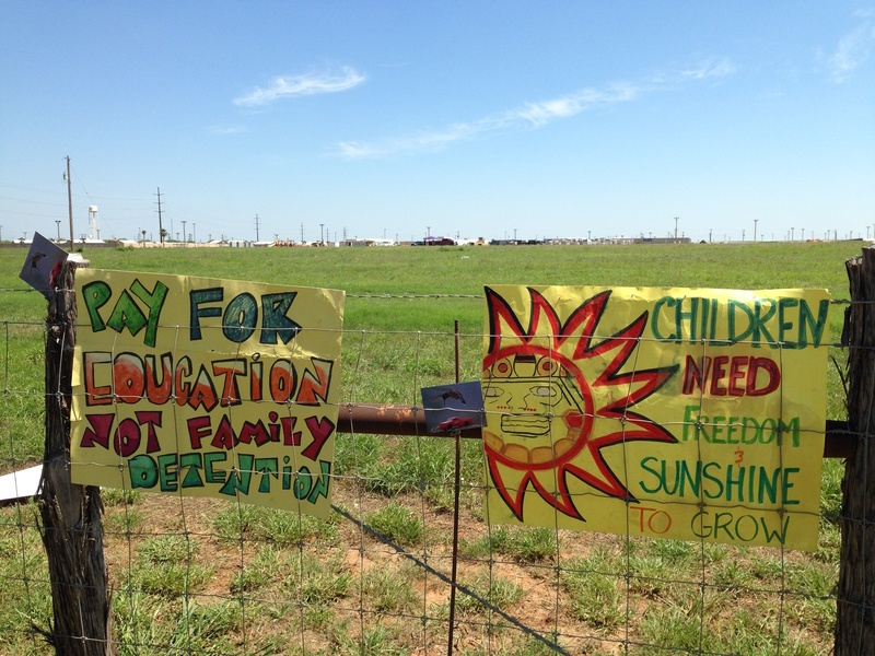 Protestors left their signs on the fence surrounding the South Texas Family Residential Center near Dilley, Texas on May 2, 2015. Photo by Ryan McCrimmon.